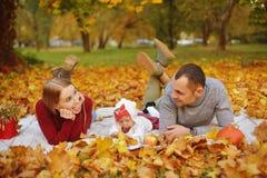 Los pares en amor están mintiendo en las hojas caidas otoño en un parque, mintiendo en la manta, disfrutando de un día hermoso de fotografía de archivo