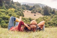 Los pares en amor se basan sobre la colina verde en lado del país imagen de archivo libre de regalías