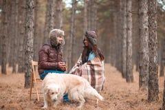 Los pares en amor se sientan en bosque con un perro, comunican y beben té de las tazas imágenes de archivo libres de regalías