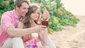 Los pares en amor, sirven asombrosamente a su socio con el anillo de compromiso en la playa almacen de metraje de vídeo