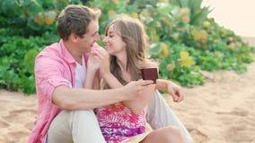 Los pares en amor, sirven asombrosamente a su socio con el anillo de compromiso en la playa almacen de video