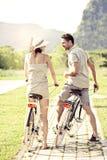 Los pares en amor tienen un paseo con las bicicletas en la naturaleza fotografía de archivo libre de regalías