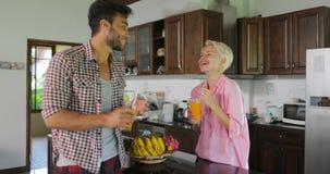 Los pares en cocina beben a Juice In Morning anaranjado, hombre joven y desayuno que habla de la mujer almacen de video