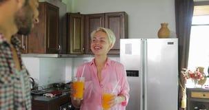 Los pares en cocina beben a Juice In Morning anaranjado, hombre joven y desayuno que habla de la mujer metrajes
