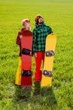 Los pares en deporte llevan con las snowboard que se colocan en la hierba y el w Foto de archivo