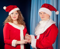 los pares en el amor que desgasta los sombreros de Santa acercan al árbol de navidad. Mujer y ajustado gordos Fotos de archivo libres de regalías