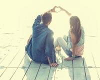 Los pares en el amor que se sienta en el embarcadero, sus manos muestran el corazón Fotografía de archivo