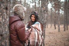 Los pares en el amor, soporte en un bosque frío del otoño y se gozan fotos de archivo libres de regalías