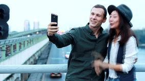 Los pares en el puente cerca del tren hacen la foto en el teléfono almacen de video