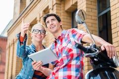 Los pares en el viaje de la ciudad que planea su Vespa viajan con la tableta foto de archivo libre de regalías