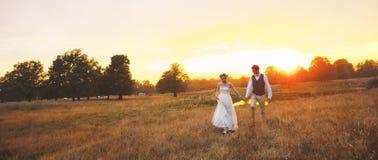 Los pares en la boda attire contra el contexto del campo en la puesta del sol, la novia y el novio Foto de archivo