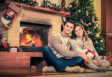 Los pares en la Navidad adornaron el interior de la casa Foto de archivo libre de regalías