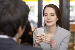 Los pares en restaurante desayunaron, mujer están en el teléfono, SMS, su Fotos de archivo