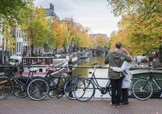 Los pares en una actitud romántica gozan de los canales de Amsterdam Imágenes de archivo libres de regalías