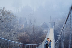 Los pares encantadores de la boda envueltos en manta se besan suavemente en el puente del sospension en las montañas Fondo de las Fotografía de archivo libre de regalías