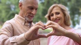 Los pares envejecidos sonrientes que muestran el corazón firman, símbolo del amor, boda feliz, afecto foto de archivo