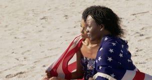 Los pares envolvieron en la bandera americana que se sentaba juntos en la playa 4k almacen de video