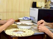 Los pares están preparando las bolas de masa hervida en la cocina imagenes de archivo