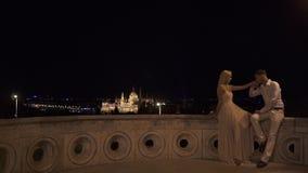 Los pares fabulosos que se besaban apasionado en Budapest magnífica empañaron el fondo en la noche almacen de video