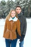 Los pares felices al aire libre en el amor que presenta en invierno frío resisten Foto de archivo libre de regalías