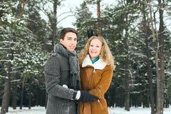 Los pares felices al aire libre en el amor que presenta en invierno frío resisten Imagenes de archivo
