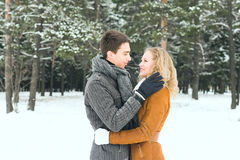 Los pares felices al aire libre en el amor que presenta en invierno frío resisten Foto de archivo