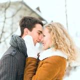 Los pares felices al aire libre en el amor que presenta en invierno frío resisten Imágenes de archivo libres de regalías