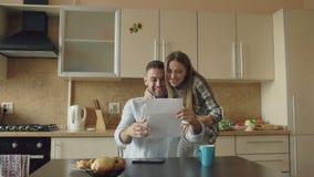 Los pares felices atractivos reciben la letra del despliegue de las buenas noticias en la cocina mientras que desayune en casa metrajes