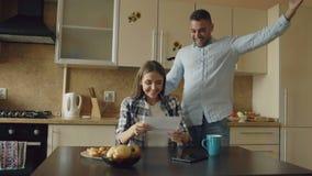 Los pares felices atractivos reciben la letra del despliegue de las buenas noticias en la cocina mientras que desayune en casa almacen de video