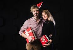 Los pares felices celebran la sonrisa roja de los presentes caja, del hombre y de la mujer que mira la cámara que abraza, en fond Fotos de archivo