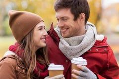 Los pares felices con el café que camina en otoño parquean Imagen de archivo
