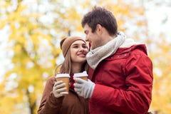 Los pares felices con el café que camina en otoño parquean Fotografía de archivo libre de regalías