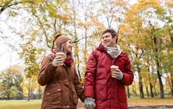 Los pares felices con el café que camina en otoño parquean Imagenes de archivo