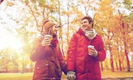 Los pares felices con el café que camina en otoño parquean Foto de archivo