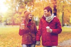 Los pares felices con el café que camina en otoño parquean Foto de archivo libre de regalías