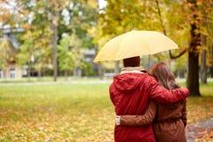 Los pares felices con el paraguas que camina en otoño parquean Fotos de archivo libres de regalías