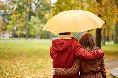 Los pares felices con el paraguas que camina en otoño parquean Foto de archivo libre de regalías