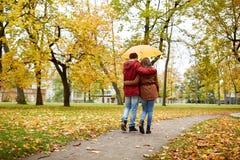Los pares felices con el paraguas que camina en otoño parquean Imagenes de archivo