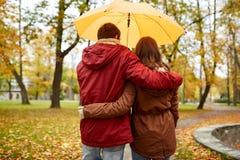 Los pares felices con el paraguas que camina en otoño parquean Imágenes de archivo libres de regalías
