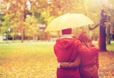 Los pares felices con el paraguas que camina en otoño parquean Foto de archivo