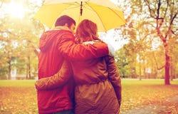 Los pares felices con el paraguas que camina en otoño parquean Imagen de archivo libre de regalías