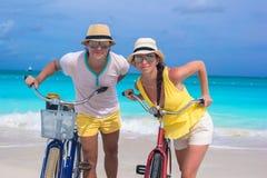 Los pares felices con las bicis el verano el Caribe vacation Fotografía de archivo libre de regalías