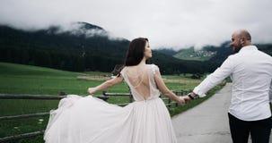 Los pares felices con ropa romántica están caminando abajo del camino del vintage del país almacen de metraje de vídeo