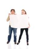 Los pares felices con un cartel aislado en un blanco Foto de archivo
