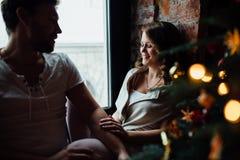 Los pares felices de amantes en pijamas se sientan en el alféizar Atmósfera de la Navidad Fotos de archivo