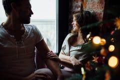 Los pares felices de amantes en pijamas se sientan en el alféizar Atmósfera de la Navidad Imágenes de archivo libres de regalías