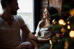 Los pares felices de amantes en pijamas se sientan en el alféizar Atmósfera de la Navidad Imagen de archivo