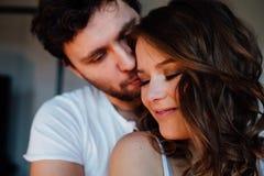 Los pares felices de amantes en pijamas sirven el abarcamiento de la muchacha de detrás Ojos cerrados Imagen de archivo libre de regalías
