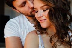 Los pares felices de amantes en pijamas sirven el abarcamiento de la muchacha de detrás Ojos cerrados Foto de archivo libre de regalías
