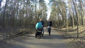 Los pares felices de la familia caminan con el carro de bebé en el bosque 4K de la primavera metrajes